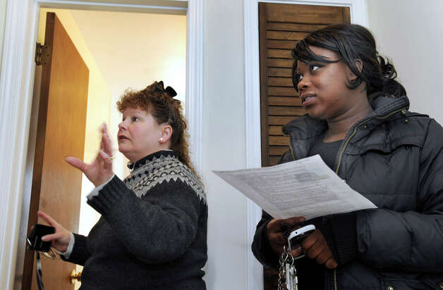 Carolyn Ridenour, 47, left, of Prudential Connecticut Realty, shows Ranisha Green, 25, of Danbury, the upstairs of an apartment for rent at Racing Brook Meadow 1 in Danbury, Conn. Tuesday, March 5, 2013 Photo: Carol Kaliff / The News-Times