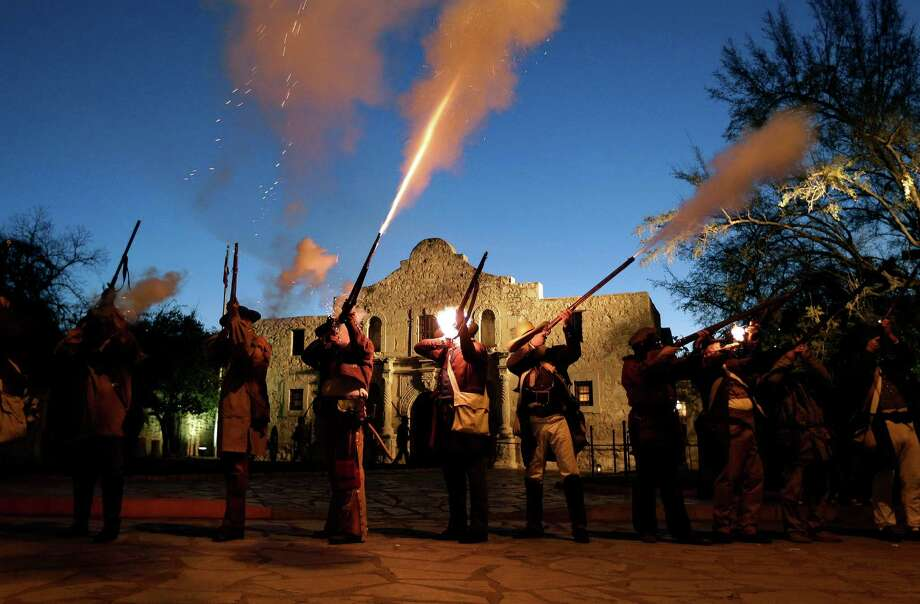 Members of the San Antonio Living History Association fire muskets Wednesday as they take part in a pre-dawn memorial ceremony to remember the 1836 Battle of the Alamo and those who fell on both sides. Photo: Eric Gay, STF / AP