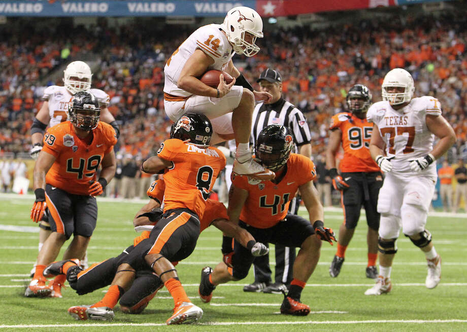 Texas quarterback David Ash (14) affirmed his status as a team leader with a strong performance against Oregon State in the Alamo Bowl, including a leaping touchdown run. Photo: Kin Man Hui, Staff / © 2012 San Antonio Express-News
