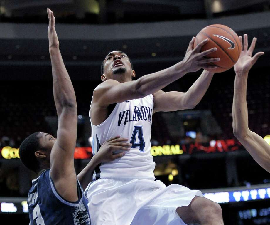 Villanova's Darrun Hilliard drives past Georgetown's Mikael Hopkins, left, during the second half of an NCAA college basketball game, Wednesday, March 6, 2013, in Philadelphia. Villanova won 67-57. (AP Photo/Michael Perez) Photo: Michael Perez