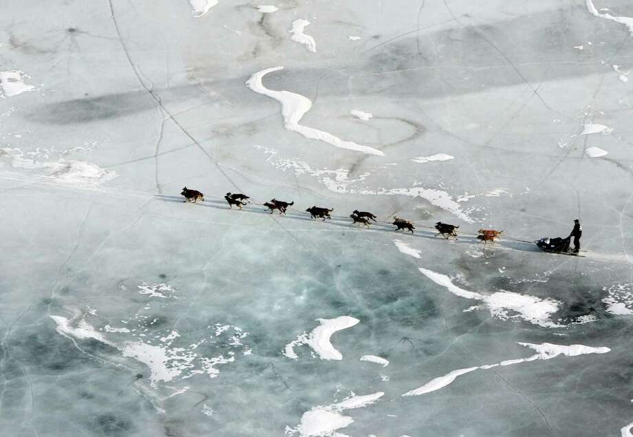 In this March 5, 2013 photo, a musher and dog team cross the ice between the Rohn and Nikolai checkpoints in Alaska during the Iditarod Trail Sled Dog Race.   (AP Photo/The Anchorage Daily News, Bill Roth) Photo: Bill Roth