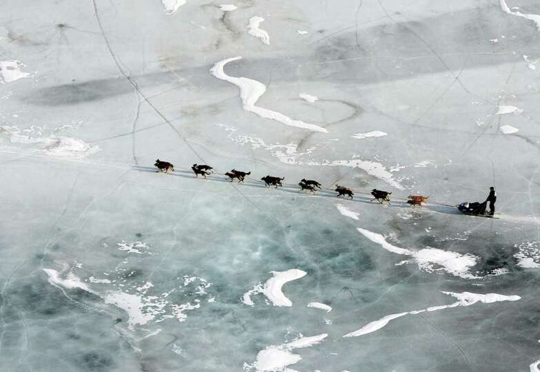 In this March 5, 2013 photo, a musher and dog team cross the ice between the Rohn and Nikolai checkp