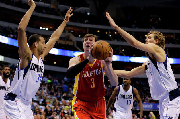 Brandan Wright and Dirk Nowitzki defend as Omer Asik goes up for a shot. Photo: Tony Gutierrez, Associated Press / AP