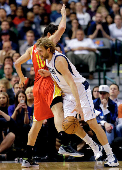Carlos Delfino fouls Dirk Nowitzki as Nowitzki drives to the basket.