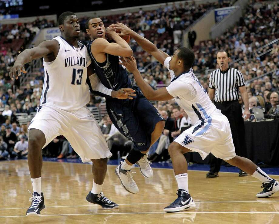 Villanova's Mouphtaou Yarou, left, and Tony Chennault clamp down on Georgetown's Markel Starks as the Wildcats end the Hoyas' 11-game winning streak. Photo: Michael Perez, FRE / FR168006 AP