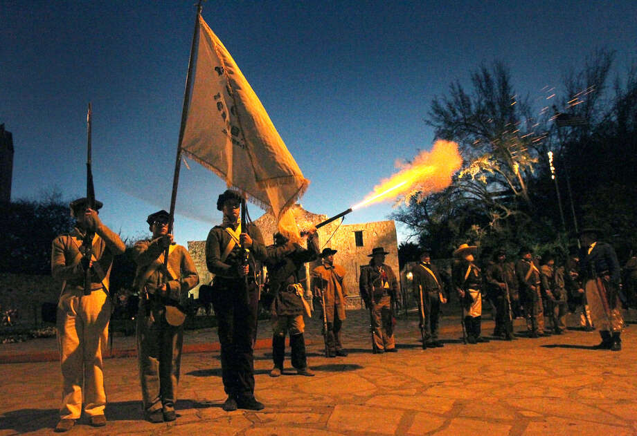 """A member of the San Antonio Living History Association fires a musket as others stand at attention in front of the Shrine of Texas Liberty during the """"Dawn at the Alamo"""" ceremony. That event and a ceremony later in the day Wednesday marked the 177th anniversary of the battle at the old mission. Photo: John Davenport / San Antonio Express-News"""