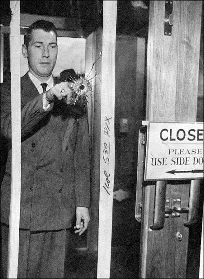 An unidentified Seattle-First National Bank employee points to the bullet hole through which Sgt. Howard Sleesman was shot. The photo was taken from inside the bank and shows crop marks made by the P-I photo department in 1954.