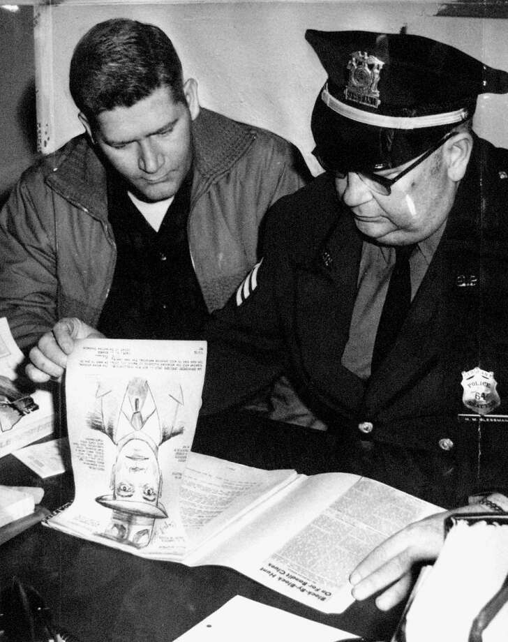 Officer Vernon Chase, left, and Sgt. Howard Slessman look at file notes in March 1963 about the 1954 Greenwood bank robbery.