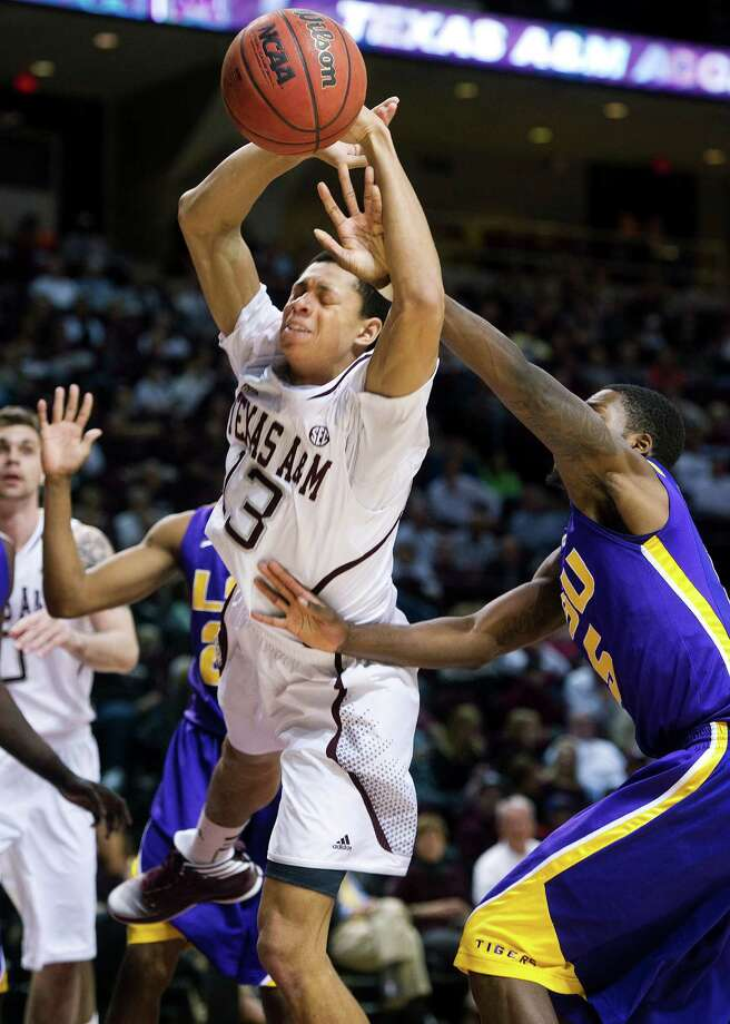 A&M's Jordan Green loses control while being harassed by LSU's Shavon Coleman, right, during the Tigers' 68-57 victory Wednesday night. Photo: Stuart Villanueva, MBR / Bryan College Station Eagle