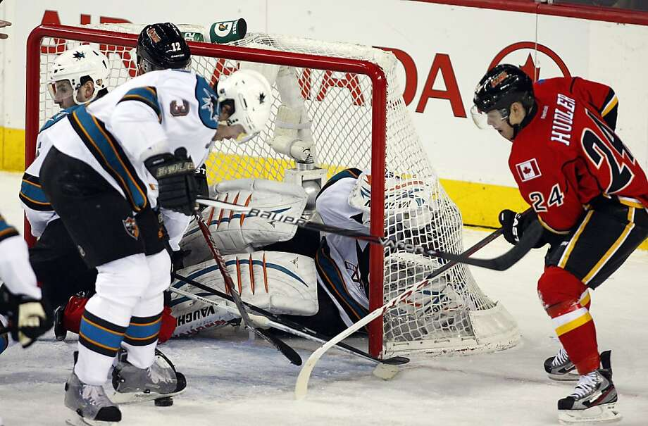 Sharks goalie Thomas Greiss tickles the twine as Douglas Murray (3) and Calgary's Jiri Hudler hover. Photo: Jeff McIntosh, Associated Press