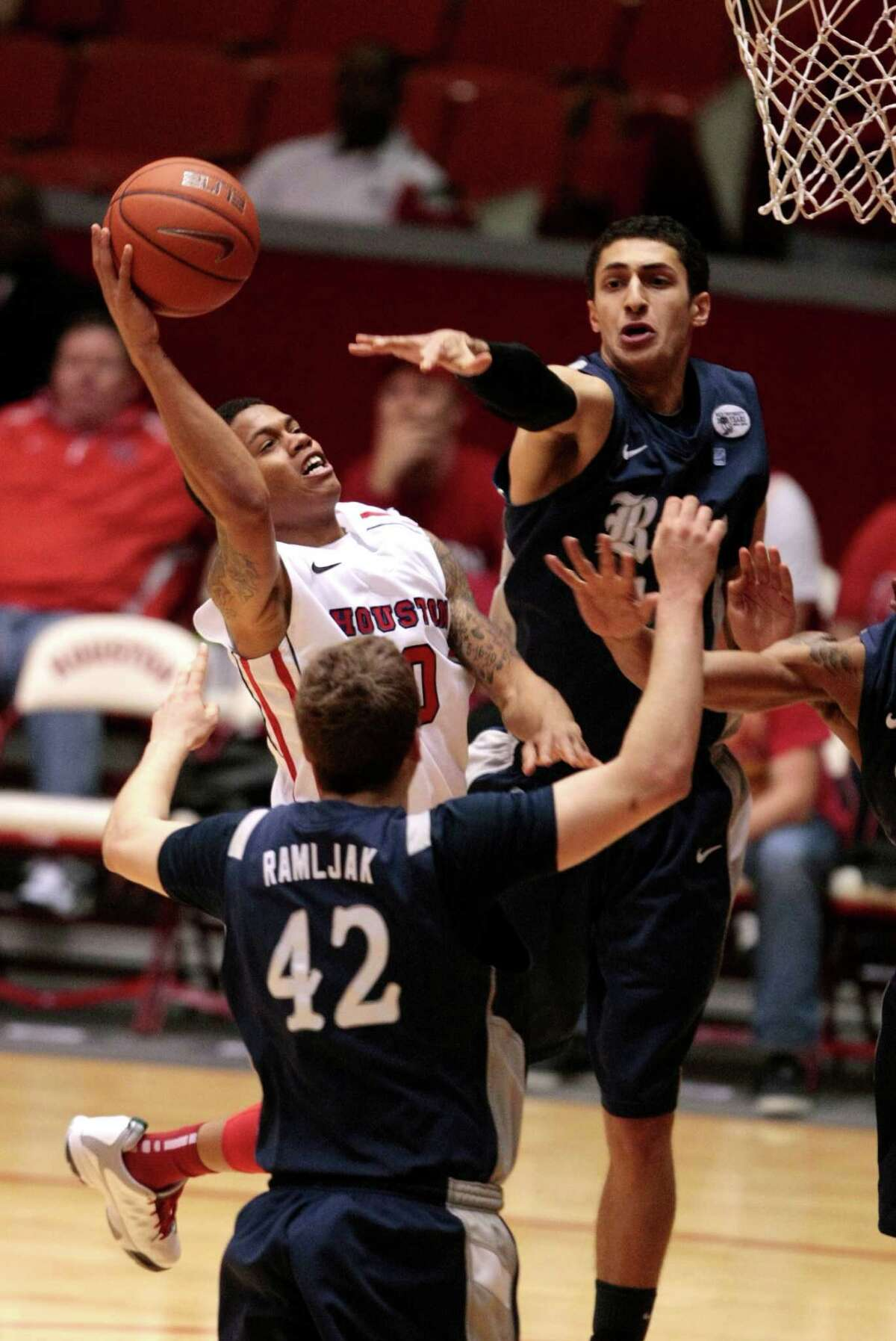 Guard Joseph Young, who led UH with 20 points, splits Rice's Austin Ramljak, left, and Bahrom Firozgary to get to the basket.