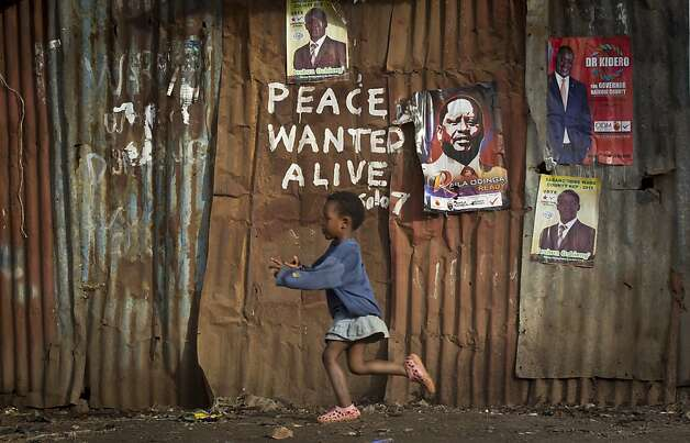 A young girl runs past pro-peace graffiti written during the post-election violence of the previous election in 2007 and a poster of presidential candidate Raila Odinga, center-right, in the Kibera slum of Nairobi, Kenya Wednesday, March 6, 2013. Election officials in Kenya transported their ballot counts to be tallied in the capital Wednesday after the preliminary electronic vote counting system broke down, while the coalition of a top presidential candidate levied charges of meddling against Britain's High Commissioner. (AP Photo/Ben Curtis) Photo: Ben Curtis, Associated Press