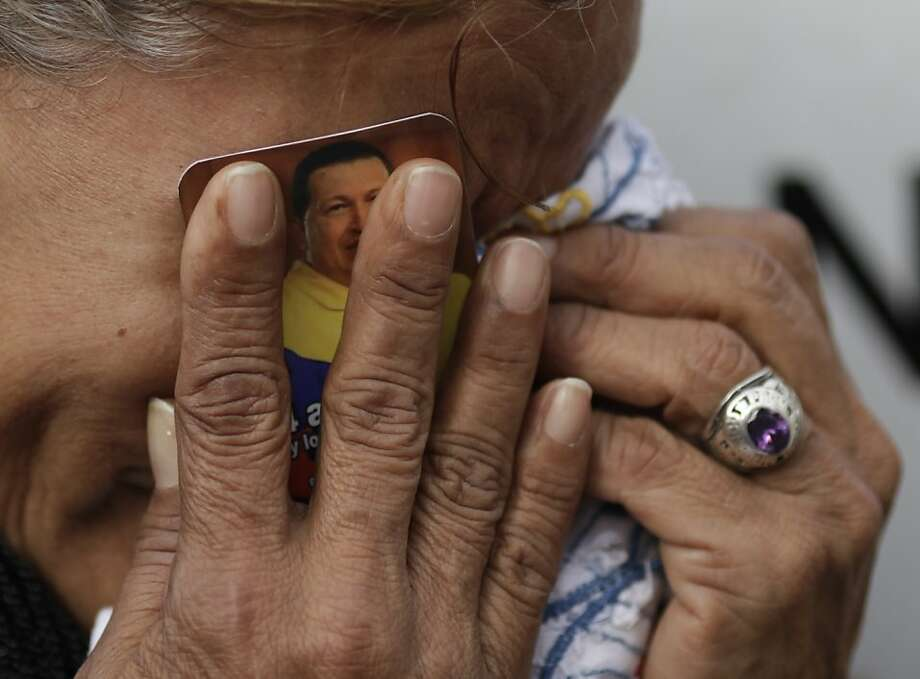 A woman holds a picture of President Hugo Chavez against her face as she cries outside the military hospital where he died Tuesday in Caracas, Venezuela, Wednesday, March 6, 2013.  Seven days of mourning were declared, all school was suspended for the week and friendly heads of state were expected  for an elaborate funeral Friday..(AP Photo/Ariana Cubillos) Photo: Ariana Cubillos, Associated Press