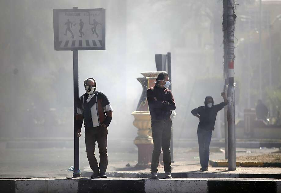 Egyptians cover their faces from tear gas during clashes between protesters and riot police near the state security building in Port Said, Egypt, Wednesday, March 6, 2013. Clashes between protesters and police have broken out in this restive Egyptian port city despite efforts by the military to separate the two sides. (AP Photo/Khalil Hamra) Photo: Khalil Hamra, Associated Press