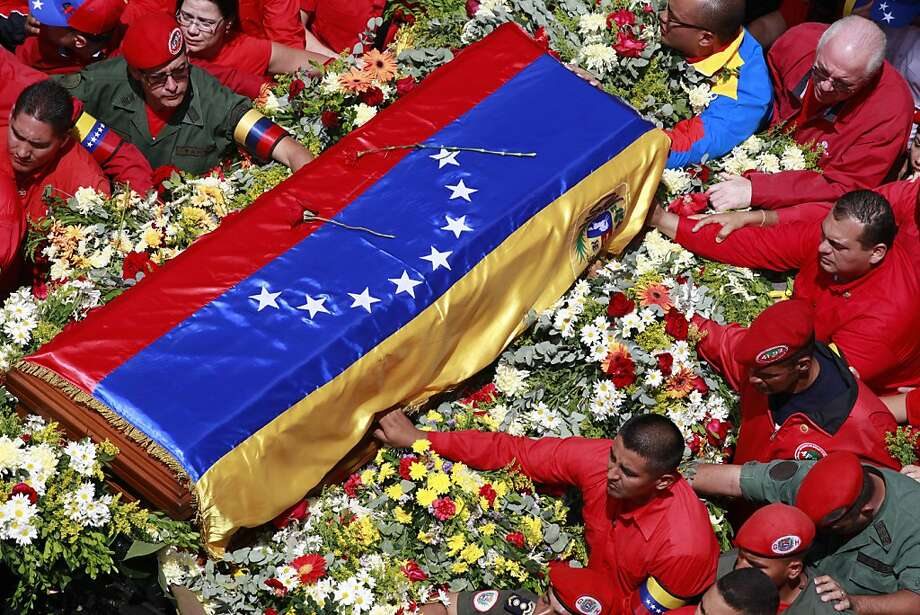 The flag-draped coffin containing the body of Venezuela's late President Hugo Chavez is taken from the hospital where he died, to a military academy, where it will remain until his funeral in Caracas, Venezuela, Wednesday, March 6, 2013. Seven days of mourning were declared, all schools were suspended for the week and friendly heads of state were expected for an elaborate funeral Friday. (AP Photo/Ricardo Mazalan) Photo: Ricardo Mazalan, Associated Press