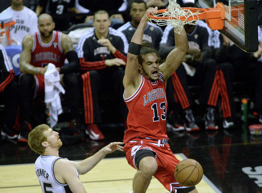 Joakim Noah of the Chicago Bulls dunks as Matt Bonner of the San Antonio Spurs trails during NBA action at the AT&T Center on Wednesday, March 6, 2013. Photo: Billy Calzada, San Antonio Express-News / San Antonio Express-News