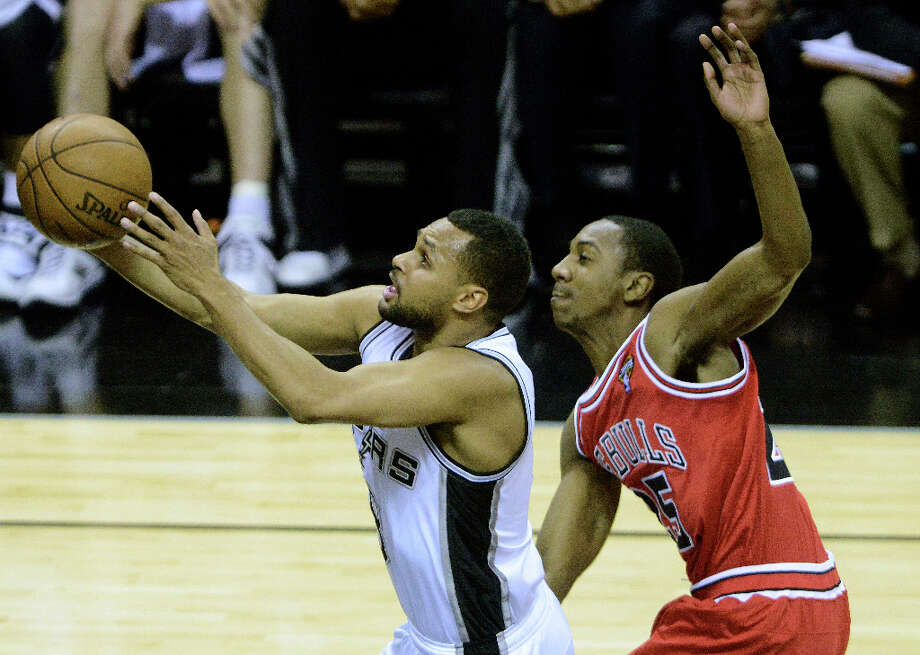 Patty Mills of the Spurs drives as Marquis Teague of the Chicago Bulls fouls him during NBA action at the AT&T Center on Wednesday, March 6, 2013. Photo: Billy Calzada, San Antonio Express-News / San Antonio Express-News