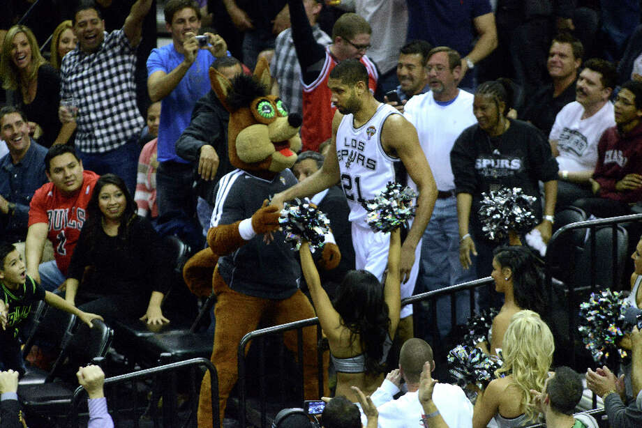 Tim Duncan of the San Antonio Spurs is greeted by the Coyote mascot and fans after his momentum caused him to run into the stands during play against the Chicago Bulls at the AT&T Center on Wednesday, March 6, 2013. Photo: Billy Calzada, San Antonio Express-News / San Antonio Express-News