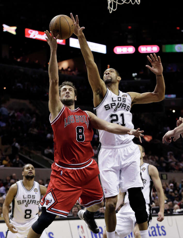 Chicago Bulls' Marco Belinelli (8) drives to the basket past San Antonio Spurs' Tim Duncan (21) during the second half of an NBA basketball game on Wednesday, March 6, 2013, in San Antonio. San Antonio won 101-83. Photo: Eric Gay, Associated Press / AP