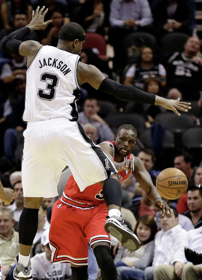 Chicago Bulls' Luol Deng, right, passes the ball around San Antonio Spurs' Stephen Jackson (3) during the first half of an NBA basketball game on Wednesday, March 6, 2013, in San Antonio. Photo: Eric Gay, Associated Press / AP