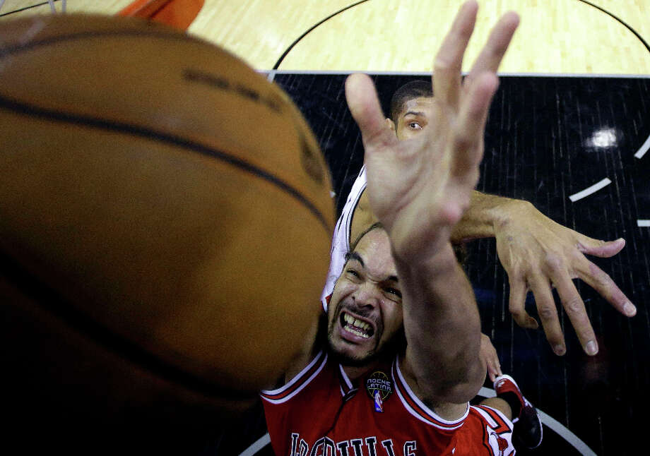 Chicago Bulls' Joakim Noah, foreground, reaches for a rebound against San Antonio Spurs' Tim Duncan during the first half of an NBA basketball game on Wednesday, March 6, 2013, in San Antonio. Photo: Eric Gay, Associated Press / AP
