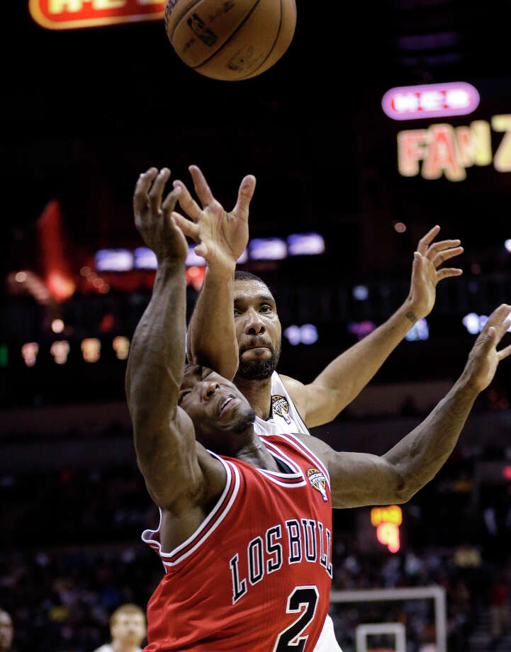 San Antonio Spurs' Tim Duncan, top, reaches over Chicago Bulls' Nate Robinson (2) for a loose ball during the first half of an NBA basketball game on Wednesday, March 6, 2013, in San Antonio. Photo: Eric Gay, Associated Press / AP