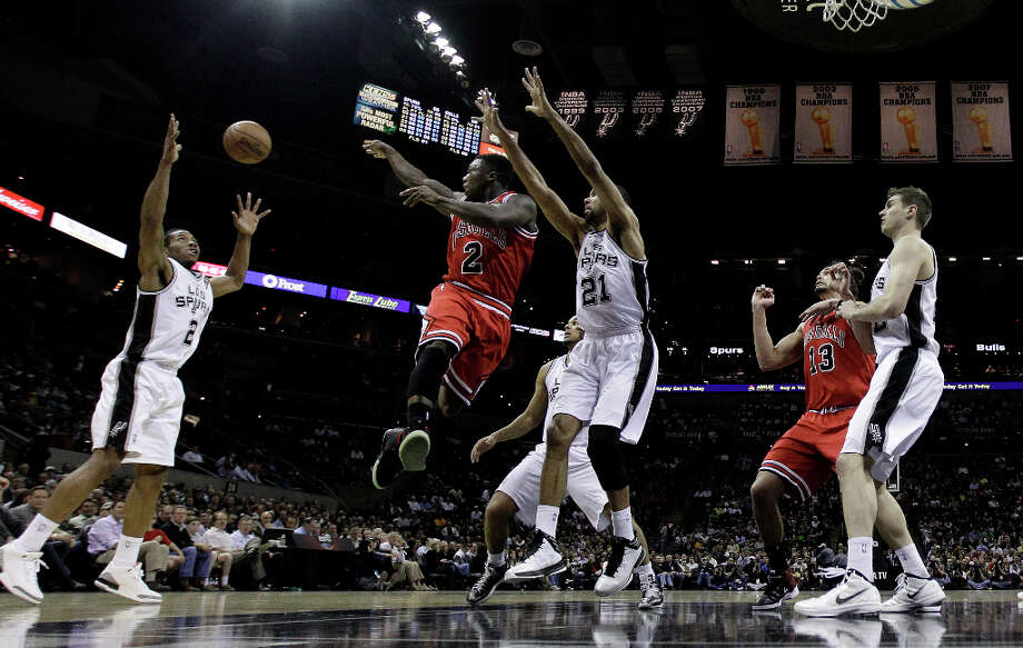 Chicago Bulls' Nate Robinson (2) passes the ball as he is pressured by San Antonio Spurs' Tim Duncan (21) during the first half of an NBA basketball game on Wednesday, March 6, 2013, in San Antonio. Photo: Eric Gay, Associated Press / AP