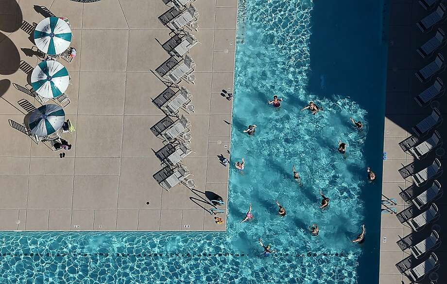 Call of the chlorine: Desert dwellers relax in a pool at a housing development in Mesa, Arizona. Phoenix home prices fell 55 percent between 2005 and 2011, but since then the housing market has rebounded, with prices up 23 percent. Photo: Justin Sullivan, Getty Images