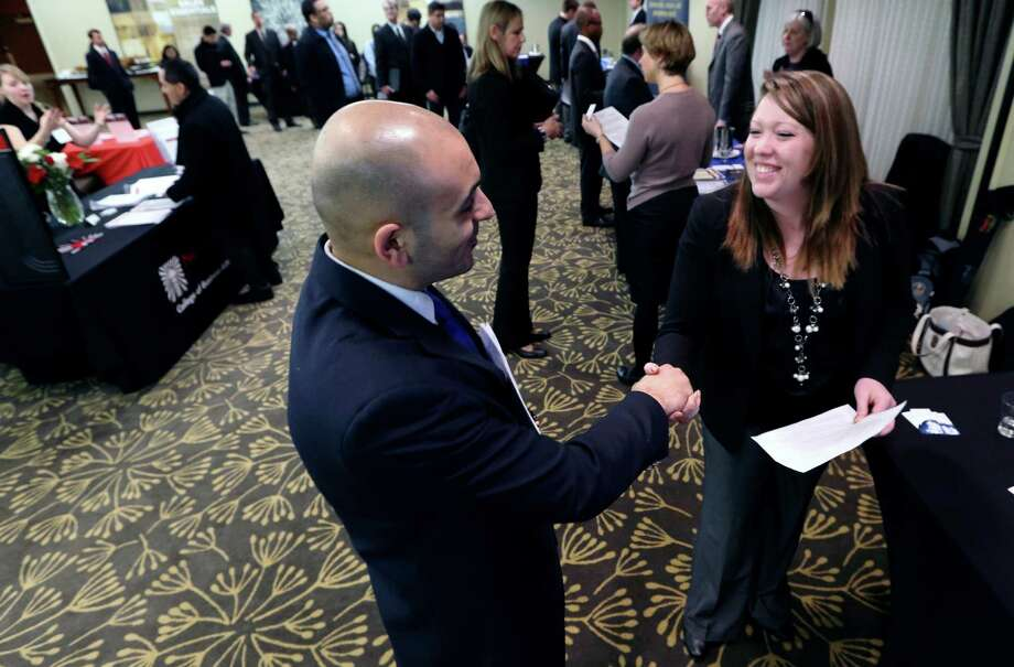 In this Monday, Feb. 25, 2013, photo, Sayed Mouawad, left, of Providence, R.I., shakes hands with Jillian Wallace of Matix, Inc., during a job fair in Boston. The number of people seeking U.S. unemployment aid fell to a seasonally adjusted 340,000 in the week ended March 2, driving down the four-week average to its lowest level in five years. Photo: Michael Dwyer