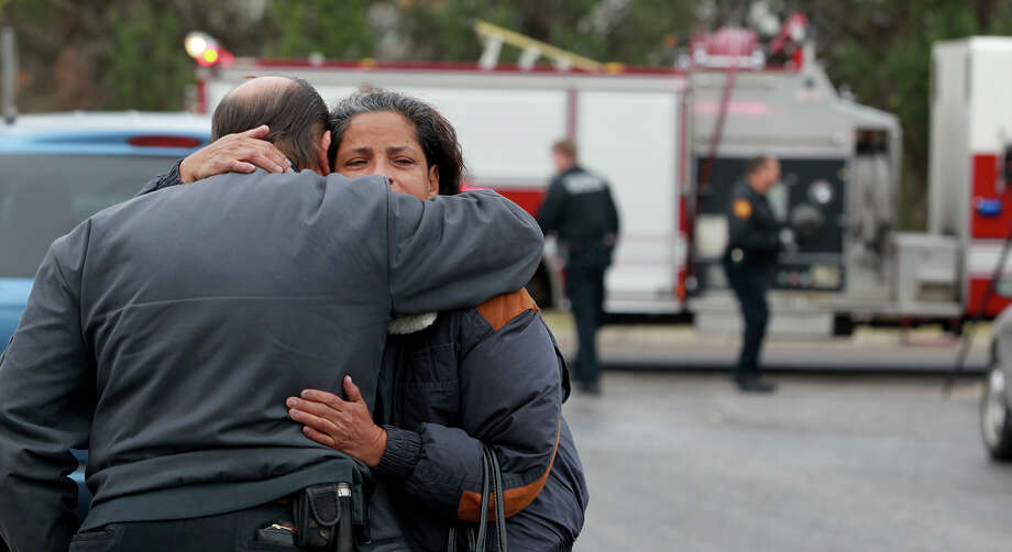 Tom Richards (facing away) hugs Anna Morris after the mobile home Morris lived in burned down early Thursday March 7, 2013. According to San Antonio Fire Department Battalion Chief B.T. McEnery, several puppies and the mother dog perished in the fire at the Cozy Cove Mobile Home and R.V. Park on the 5,200 block of Crestway Drive. The cause of the fire is being investigated and the home's other resident, Dennis James Martin, was not injured. Damages were estimated at about $60,000. Photo: JOHN DAVENPORT, SAN ANTONIO EXPRESS-NEWS / ©San Antonio Express-News/Photo may be sold to the public