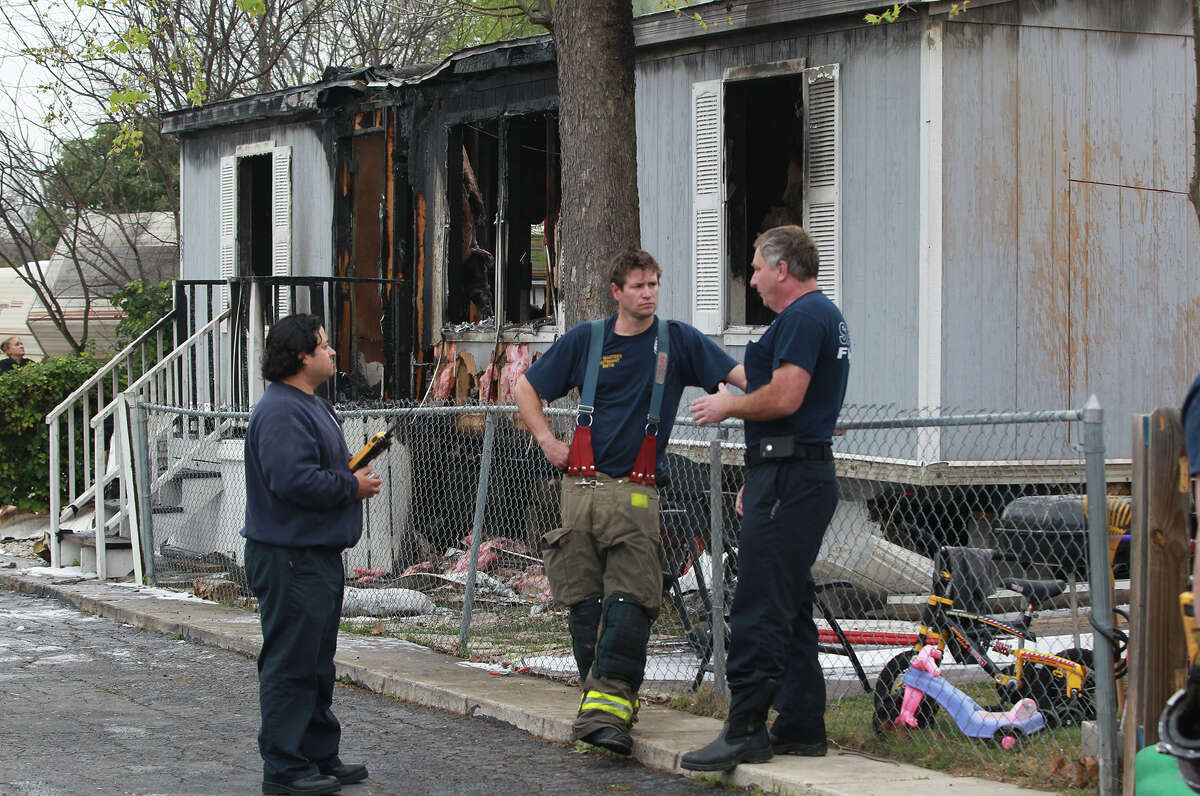 San Antonio firefighters monitor a mobile home that Anna Morris lived in that burned down early Thursday March 7, 2013. According to San Antonio Fire Department Battalion Chief B.T. McEnery, several puppies and the mother dog perished in the fire at the Cozy Cove Mobile Home and R.V. Park on the 5,200 block of Crestway Drive. The cause of the fire is being investigated and the home's other resident, Dennis James Martin, was not injured. Damages were estimated at about $60,000.