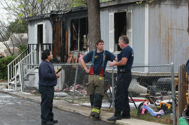 San Antonio firefighters monitor a mobile home that Anna Morris lived in that burned down early Thursday March 7, 2013. According to San Antonio Fire Department Battalion Chief B.T. McEnery, several puppies and the mother dog perished in the fire at the Cozy Cove Mobile Home and R.V. Park on the 5,200 block of Crestway Drive. The cause of the fire is being investigated and the home's other resident, Dennis James Martin, was not injured. Damages were estimated at about $60,000. Photo: JOHN DAVENPORT, SAN ANTONIO EXPRESS-NEWS / ©San Antonio Express-News/Photo may be sold to the public