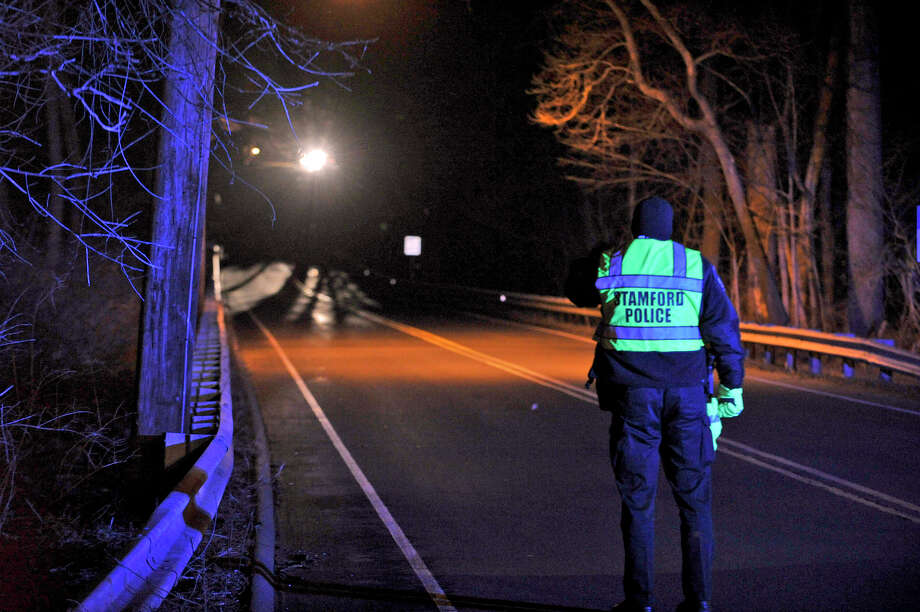 A Stamford police officer directs traffic after a tree fell on Long Ridge Road in North Stamford Wednesday night closing the road and knocking down wires. Photo: Jason Rearick