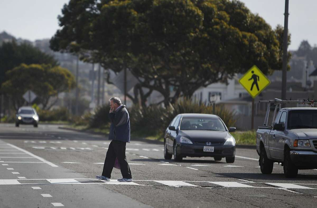 Roger Neaves of San Francisco crosses Sloat Boulevard at Vale Avenue and Forest View Drive on Tuesday, March 5, 2013 in San Francisco, Calif. A 17-year-old girl crossing Sloat Boulevard was struck and killed on Saturday night. The intersection does not have stop lights or a stop sign.