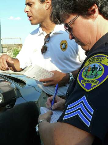 Lt. James Perez and Sgt. Sue Lussier, seen in a 2011 file photo, have been working together to assess security measures at Fairfield schools in the wake of the Newtown tragedy. In neighboring Westport, officials are squabbling over a plan to contract with a private security firm to do a schools assessment. Photo: Genevieve Reilly, File Photo / Fairfield Citizen