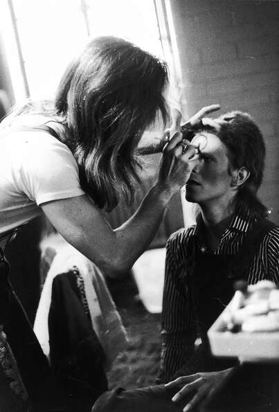Make-up artist Pierre La Roche prepares English singer David Bowie for a performance as Aladdin Sane