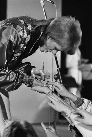 English singer, musician and actor David Bowie signs the hands of a group of female fans, circa 1974. Photo: Terry O'Neill, Getty Images / 2006 Getty Images