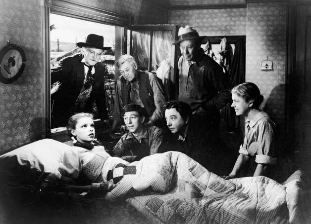 Dorothy, Judy Garland, sits up in bed while (left to right; top to bottom) Frank Morgan, Charles Grapewin, Ray Bolger, Jack Haley, Bert Lahr and Clara Blandick surround her in 'The Wizard of Oz.' Photo: MGM Studios, Getty Images / Moviepix