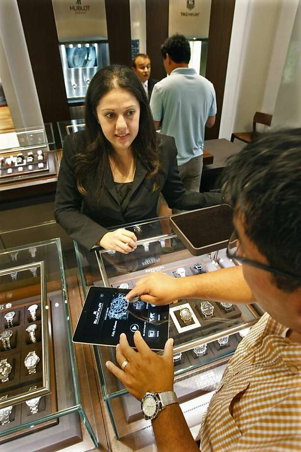 Watches are bigger and flashier than ever. Some do far more than tell time, and many are used as much for decor as to tell time. Here, Joanne Sawaya helps customer Dan Knickerbocker at the Tourneau watch store at South Coast Plaza in Costa Mesa, California. (Don Bartletti/Los Angeles Times/MCT) Photo: Don Bartletti, McClatchy-Tribune News Service