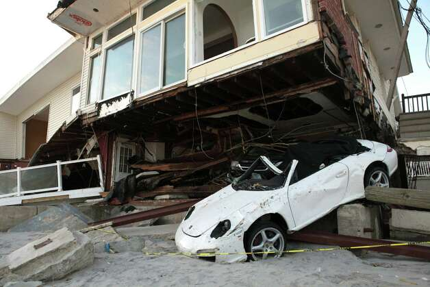 Beachfront homes lie in ruin in the aftermath of Hurricane Sandy in the Rockaways, N.Y. American forecasts initially indicated the deadly storm would stay out to sea, but European models proved more accurate. Photo: Steven Greaves / © Corbis.  All Rights Reserved.