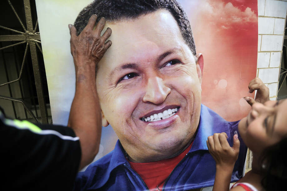 A girl helps a man to hang a poster with a portrait of the late Venezuelan President Hugo Chavez at the 23 de Enero neighborhood in Caracas on March 7, 2013. Countless Venezuelans filed past the remains of president Hugo Chavez on Thursday, crying, making the sign of the cross and giving military salutes as an era ended and elections loomed in the oil-rich nation. Photo: EITAN ABRAMOVICH, AFP/Getty Images / 2013 AFP