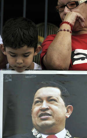 A boy looks at poster with a portrait of late Venezuelan President Hugo Chavez at the 23 de Enero neighborhood in Caracas on March 7, 2013. Countless Venezuelans filed past the remains of president Hugo Chavez on Thursday, crying, making the sign of the cross and giving military salutes as an era ended and elections loomed in the oil-rich nation. Photo: EITAN ABRAMOVICH, AFP/Getty Images / 2013 AFP