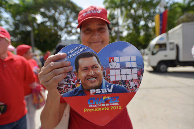 A woman shows a picture of Hugo Chavez as she waits to access the chapel where body of President Hugo Chavez remains on March 07, 2013 in Caracas, Venezuela. Photo: LatinContent/STR, LatinContent/Getty Images / 2013 Latin Content