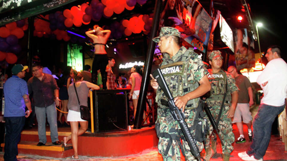 Mexican navy marines patrol the nightclub section as Spring Break revelers enjoy in the resort city