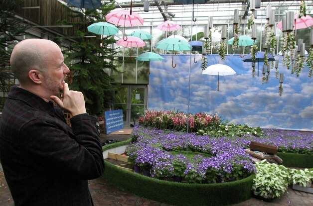 "Atlanta Botanical Garden's Landscape Design & Planning Manager Tres Fromme talks about the bowler hats, umbrellas and upside down orchids are features in the Rene Magritte themed Orchid Atrium as part of the garden's ""Orchid Daze: Surreal Beauty,"" show of fanciful flowers and playful objects, February 8, 2013. Photo: Phil Skinner, MCT / Atlanta Journal-Constitution"