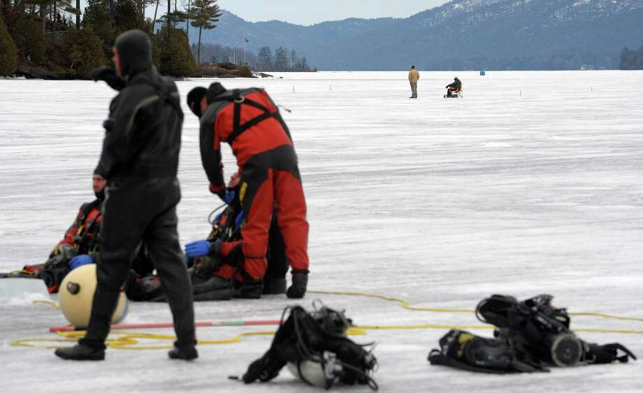 Ice fishermen are seen in the background as New York State Police and Delaware State Police divers went through training exercises on Lake George on Thursday, March 7, 2013 in Lake George, NY.    (Paul Buckowski / Times Union) Photo: Paul Buckowski, Albany Times Union / 10021416A