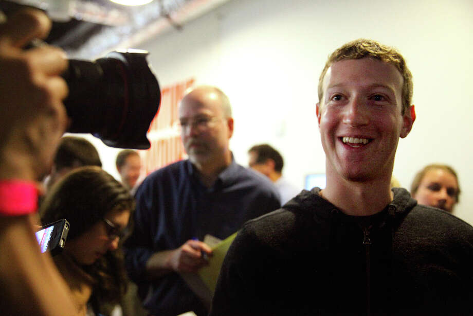 Mark Zuckerberg (center) speaks to a media after a press conference where a redesign of  Facebook's  News Feed was announced at it's headquarters on Thursday, March 7, 2013 in Menlo Park, Calif. Photo: Lea Suzuki, The Chronicle / ONLINE_YES