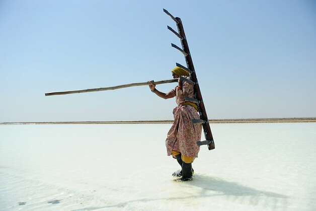 TOPSHOTS  Indian salt  worker Walbai Ayyubbhai, 70, carries a rake at a salt pan on the eve of International Women's Day in the Santalpur region of Little Rann of Kutch, some 240 kms from Ahmedabad on March 7, 2013. Women have always faced higher unemployment rates than men, and the sluggish global economy in recent years has only made the situation worse, the International Labour Organisation said in December 2012.  AFP PHOTO / Sam PANTHAKYSAM PANTHAKY/AFP/Getty Images Photo: Sam Panthaky, AFP/Getty Images