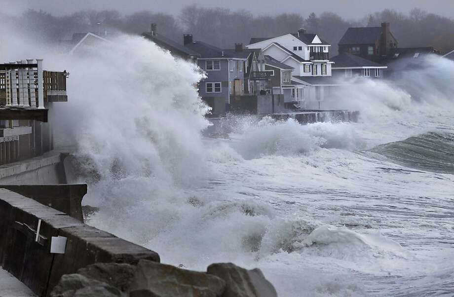 Ocean waves crash over a seawall and into houses along the coast in Scituate, Mass., Thursday, March 7, 2013. A nor'easter is bringing wind-whipped, wet snow to Massachusetts, and coastal flooding is expected in communities still recovering from February's blizzard. (AP Photo/Steven Senne) Photo: Steven Senne, Associated Press