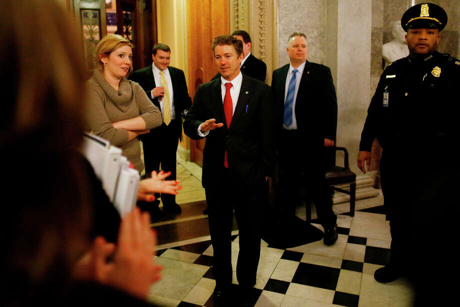 Sen. Rand Paul, R-Ky., walks off the floor of the Senate to applause after his filibuster of the nomination of John Brennan to be CIA director on Capitol Hill in Washington, early Thursday, March 7, 2013. Senate Democrats pushed Wednesday for speedy confirmation of John Brennan's nomination to be CIA director but ran into a snag after Paul began a lengthy speech over the legality of potential drone strikes on U.S. soil. But Paul stalled the chamber to start what he called a filibuster of Brennan's nomination. (AP Photo/Charles Dharapak) Photo: Charles Dharapak, Associated Press / AP
